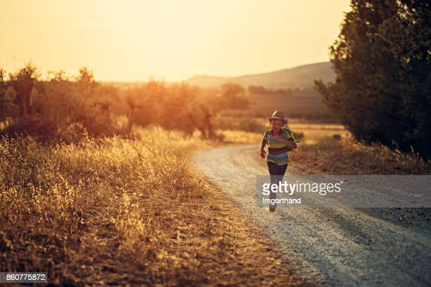 Little boy with backpack running on dirt road