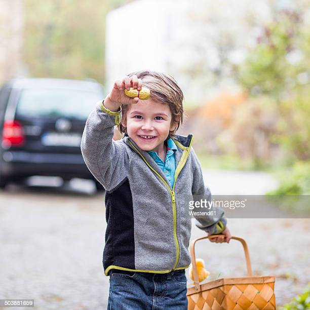 Little boy with basket proudly presenting his found chocolate Easter bunny