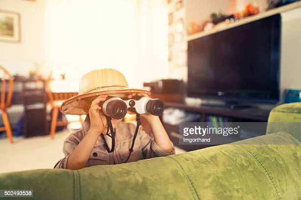 Little boy with binoculars exploring living room