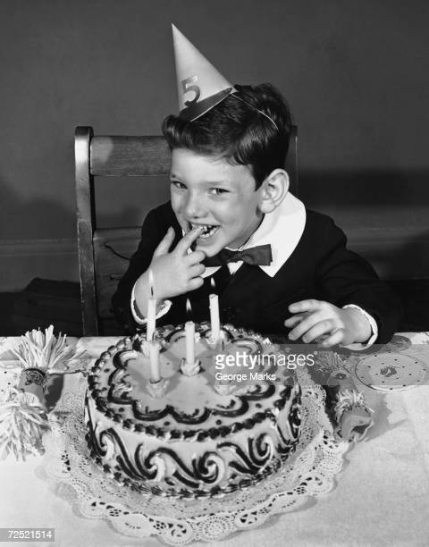 Little boy with birthday cake and party hat