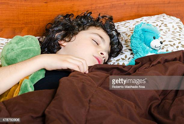 Little boy with black hair sleeping with his blue teddy bear and green turtle covered with a brown comforter