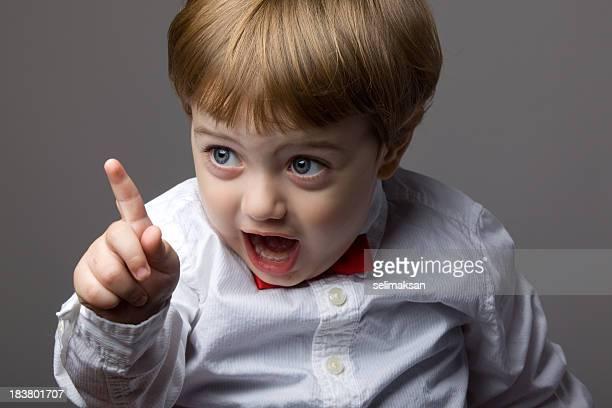 Petit garçon avec des cheveux blonds Secouer son doigt pour attention