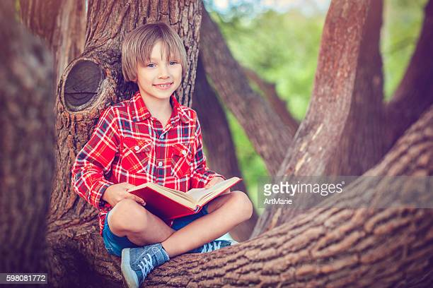 Little boy with book in autumn