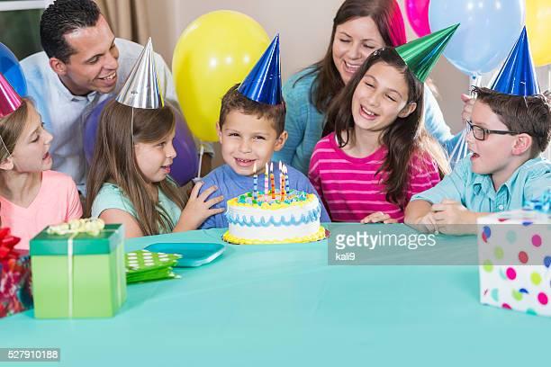 Petit garçon avec un gâteau, la famille, les amis à la fête d'anniversaire