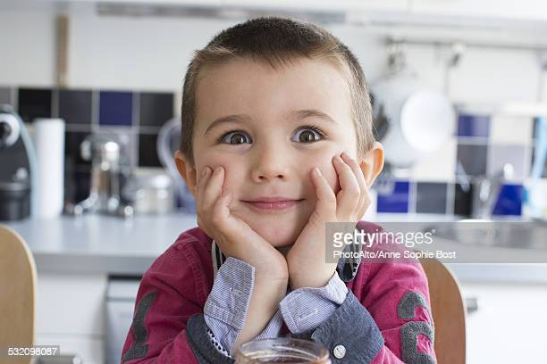 Little boy with chin resting on hands, looking surprised
