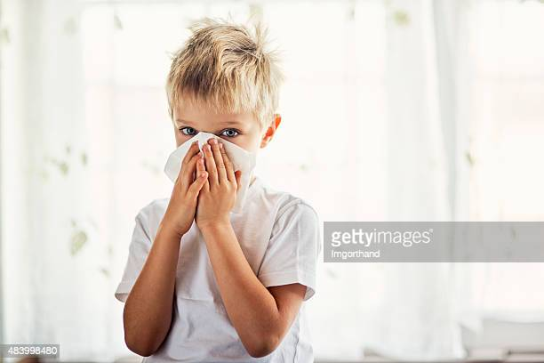 Little boy with cold cleaning his runny nose.