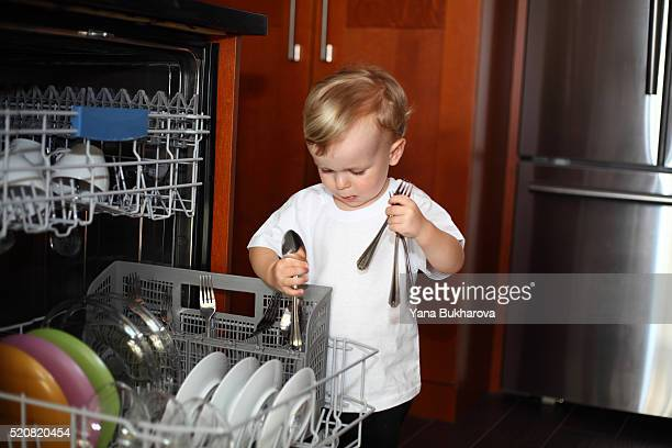 Little boy with cutlery near the dishwasher