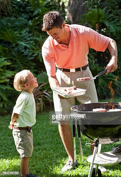 Little boy with dad grilling hotdogs and burgers