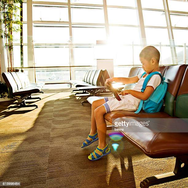 Little boy with digital tablet waiting in the airport