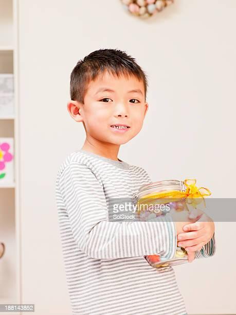 Kleiner Junge mit Ostereiern in einem Gefäß