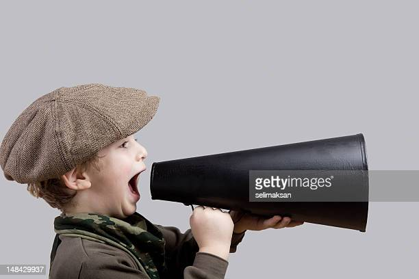 Little boy with flat cap shouting on old fashioned megaphone