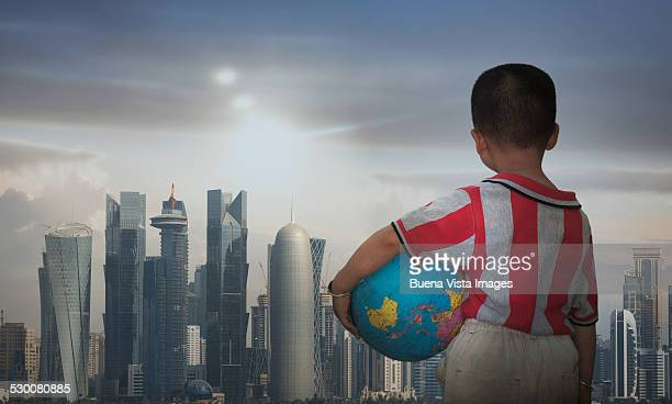 Little boy with globe watching a city