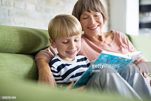 Little boy with his grandmother reading a book