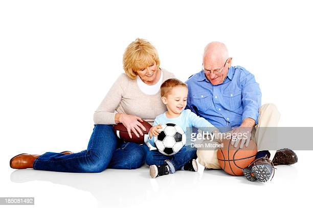 Little boy with his grandparents sitting on white