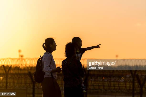 A little boy with his mother and grandmother watch the sunset scenery at Beijing international airport