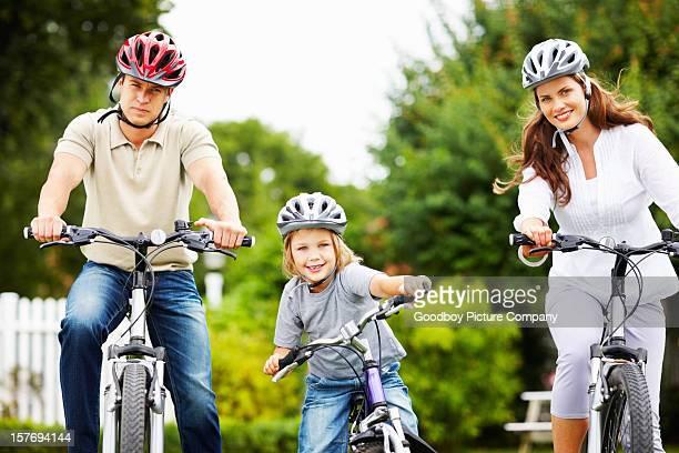 Petit garçon avec ses parents équitation de vélo