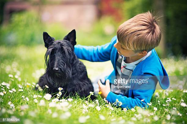 Little boy with his pet pal lying on spring grass