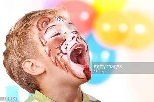 Little boy with lion face paint on birthday party