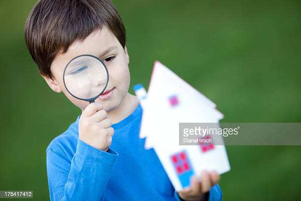 little boy with loupe looking house-miniature