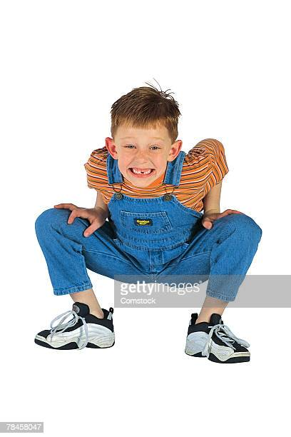 Little boy with missing tooth squatting