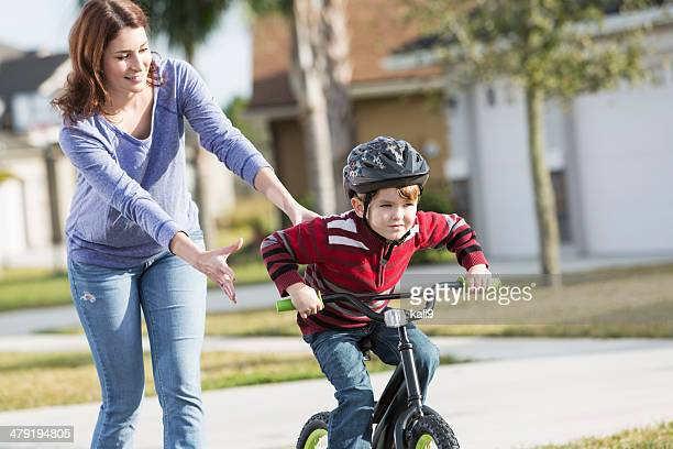 Little boy with madre, aprender a montar en bicicleta