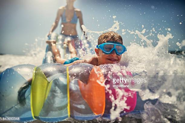 Little boy with mother playing having fun in sea