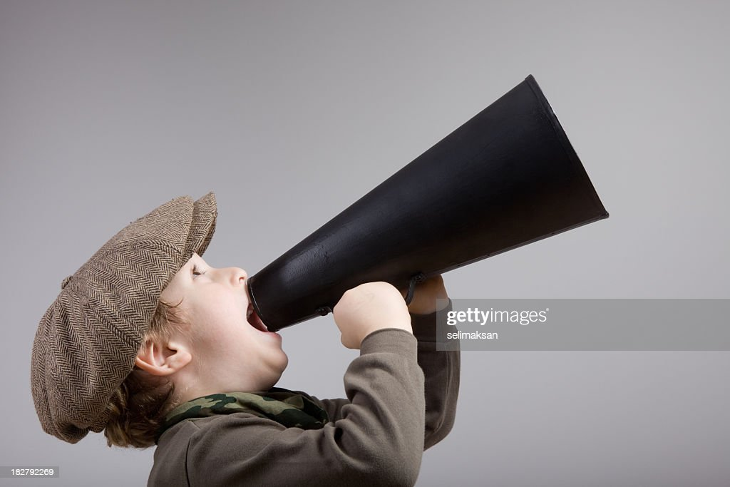 Little boy with newsboy cap shouting on old fashioned megaphone : Stock Photo