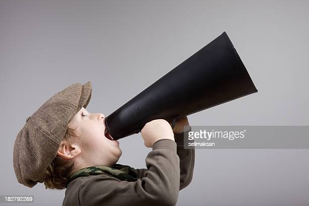 Little boy with newsboy cap shouting on old fashioned megaphone