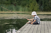 Little boy with old-fashioned fishing rod on a wooden pier