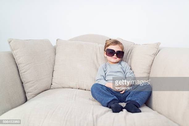Little boy with oversized sunglasses sitting on couch