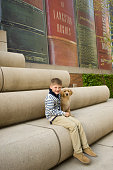 Little boy with puppy sits by giant books