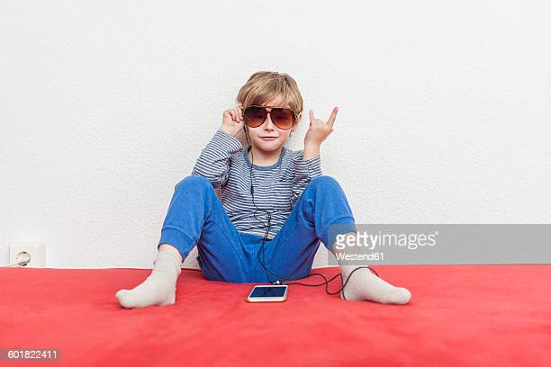 Little boy with sunglasses sitting on bed hearing music with smartphone and earphones