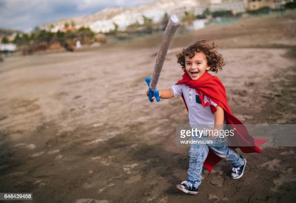 Little boy with sword and cape running on the beach