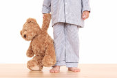 boy in pijama with his teddy bear isolated on white