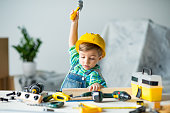 Cute little boy in yellow hard hat holding wooden plank and toy hammer