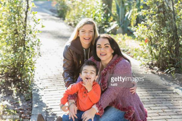 Little boy with two mothers  in the park