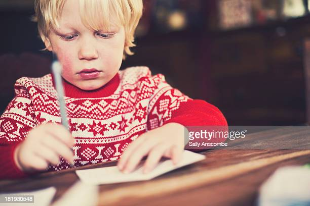 Little boy writing a card