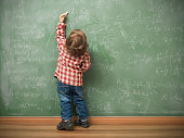 Little boy writing on green blackboard with math formulas written on.He is wearing a red plaid shirt and standing on the left side of frame.The green board is full of mathematics and physics formulas.