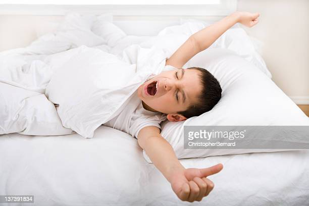 Little boy yawning and stretching in bed