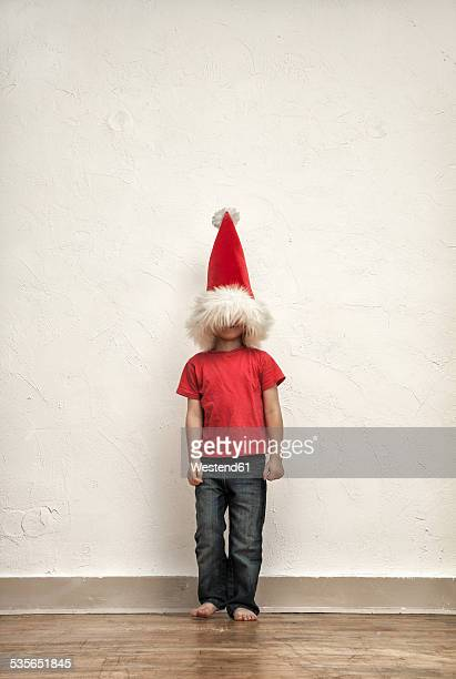 Little boys face hiding under oversized Christmas cap