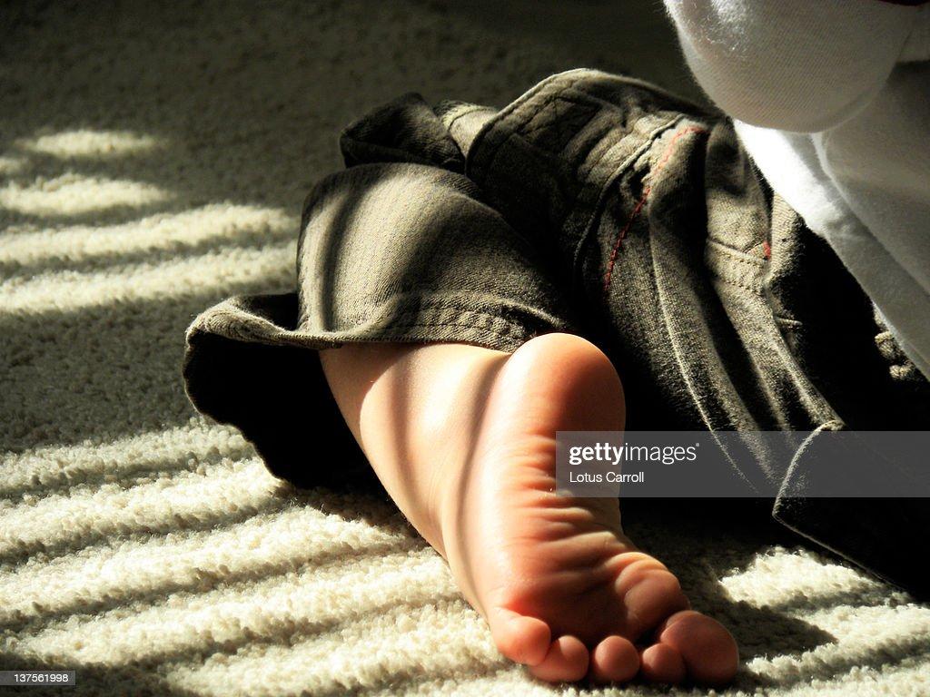 Little boy's foot on carpet in sunlight : Stock Photo