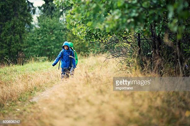 Kleine Jungen Wanderungen bei Regen
