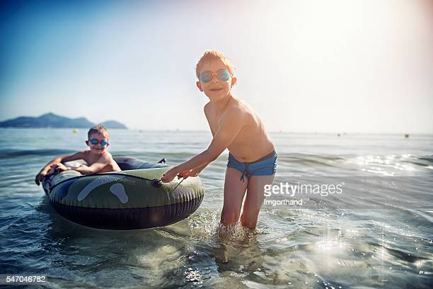 Little boys playing at sea with inflatable boat