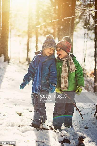 Kleine Jungen spielen in winter forest