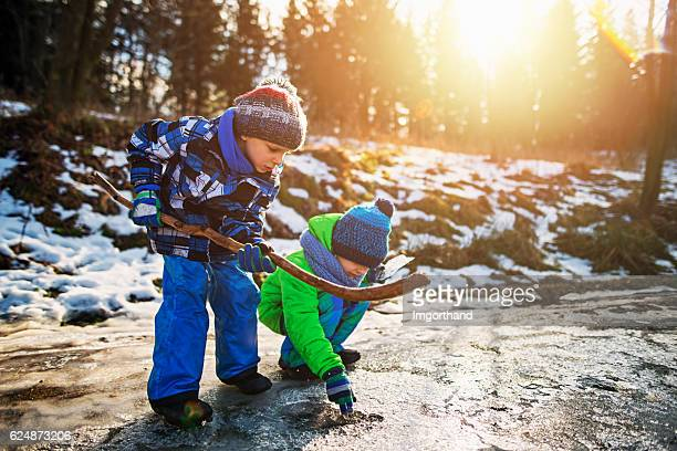 Little boys playing with a frozen puddle in winter