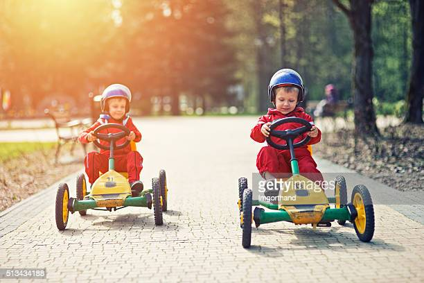Little boys racing on pedal go-karts