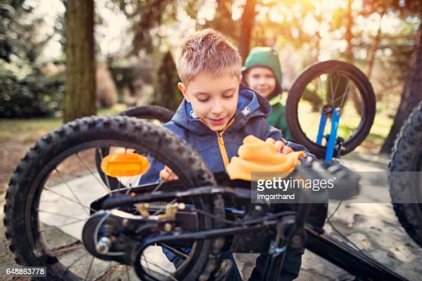 Little boys tending to their bicycles after winter