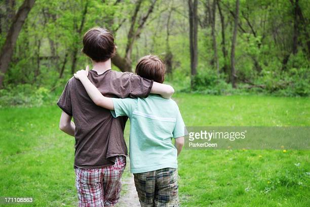 Little Boys Walking Along Path in Wooded Green Park
