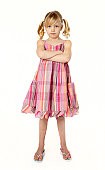 Full length studio photo of 5 year old girl with arms crossed, looking defiantly at camera.
