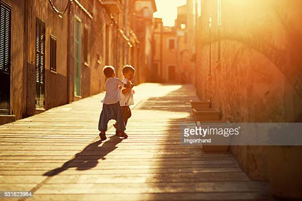 Little brothers playing in a  mediterranean street